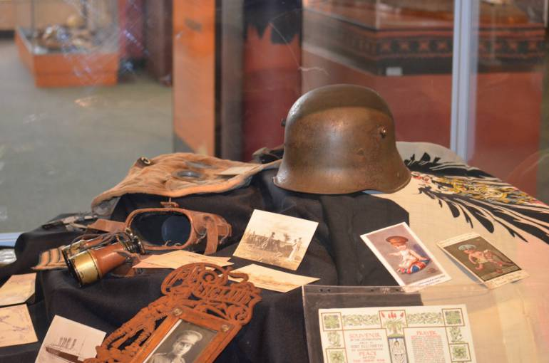 The exhibit includes artefacts from the Museum's collection including an original WWI German officer's helmet